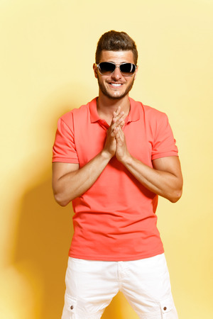 metrosexual: Young brunette man in sunglasses with stubble posing looking at camera folded his arms in front of him and smiles while standing against yellow background. Stock Photo