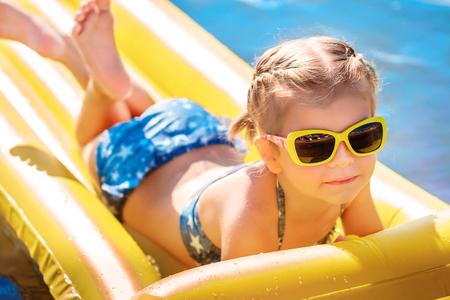 Petite fille dans des lunettes de soleil qui nagent sur un matelas de plage gonflable. Banque d'images - 82402046