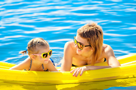 Mother and daughter in sunglasses floating on airbed together. Zdjęcie Seryjne