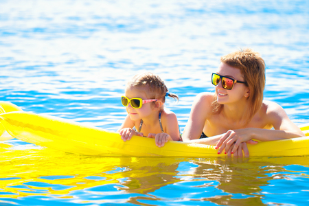 Mother and daughter in sunglasses floating on airbed together. Stock Photo
