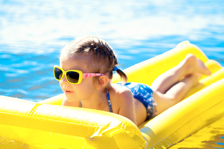 Little girl in sunglasses swimming on inflatable beach mattress. Stock Photo