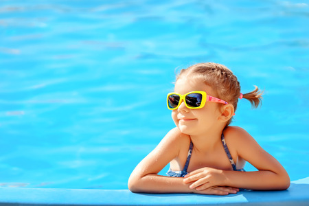 Smiling cute little girl in sunglasses in pool in sunny day. Stock Photo