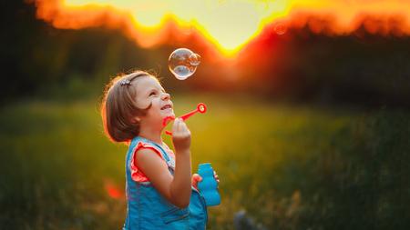 Fille de cinq ans caucasien enfant soufflant des bulles de savon en plein air au coucher du soleil - heureuse enfance insouciante Banque d'images - 82731381