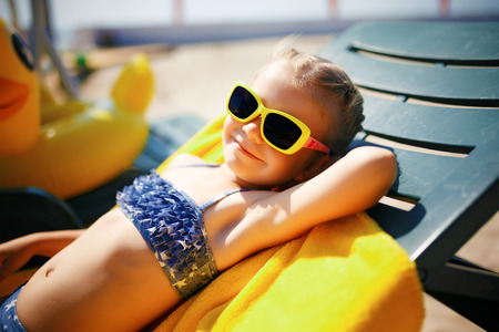 little girl in sunglasses is sunbathing on a sunbed near the pool at the resort