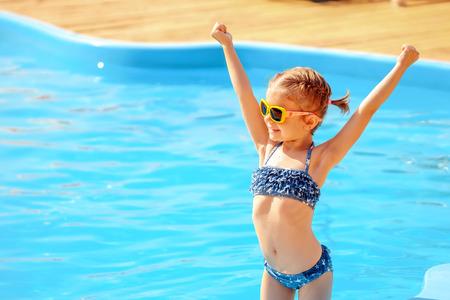 夏の休暇の概念。スイミング プールのそば手を繋いでいるサングラスでかわいい女の子。