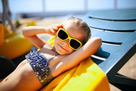 Petite fille dans les lunettes de soleil est bronzer sur une chaise longue près de la piscine de la station Banque d'images - 82731419