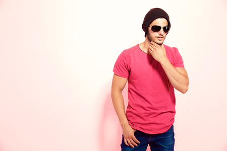 Hipster guy in sunglasses wearing brown hat and pink t-shirt touching chin holding hand in pocket. Stock Photo