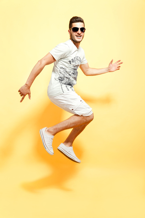 Shot of handsome bearded guy dressed in white t-shirt and shorts jumping looking at camera smiling. Stock Photo