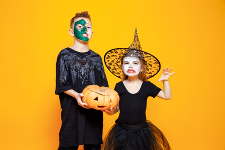 niños vistiendose: Muchachos de los niños y la muchacha en diversos trajes de Víspera de Todos los Santos Roscan y asustan la cámara con la calabaza aislada en fondo amarillo.