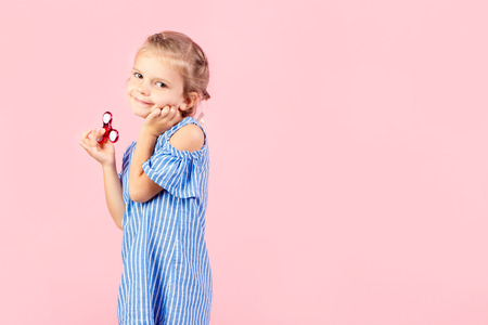 Little beautiful girl in blue stripped shirt is playing red spinner in hand