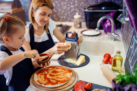Young woman wuth her little adorable daughter in formal clothing making pizza in modern kitchen at home.