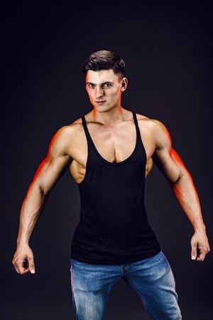 bodybuilder poseren. Mooie sportieve kerel mannelijke macht. Fitness gespierde man in het shirt op een donkere achtergrond