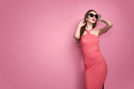 Studio サングラス笑顔とポーズでピンクの背景に赤いの官能的な唇とセクシーなドレスで若い美しいスリムなセクシーな若い女性の肖像画 写真素材
