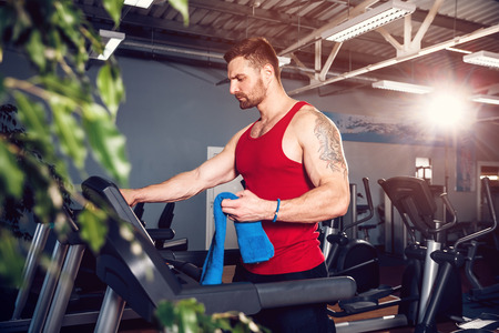 Man wiping his face with a towel beside a treadmill