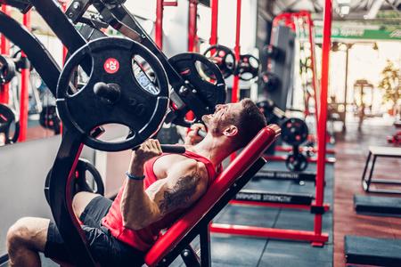 スポーツ男がジムでシミュレータに肩の運動を行います。残酷なスポーツ男。ジムでトレーニングにボディービルダー。健康とフィットネス