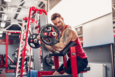 Bearded tattoed Man bodybuilder doing the set of a barbell exercise in a gym. Real time shot Stock Photo