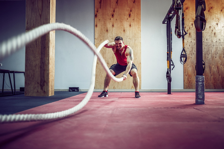Men with battle rope in functional training fitness gym