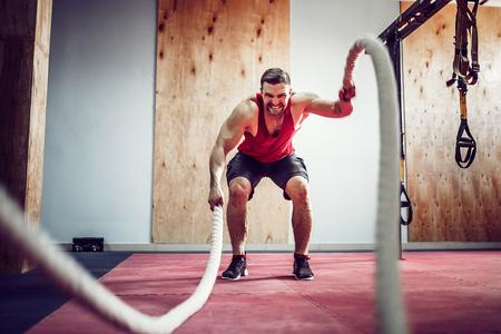 Mannen met gevechts touw in functionele training fitness gym Stockfoto