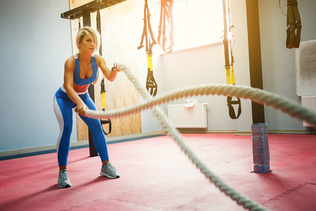 Fit blonde beautiful woman with battle ropes exercise in the fitness gym. Young female wearing sportswear.