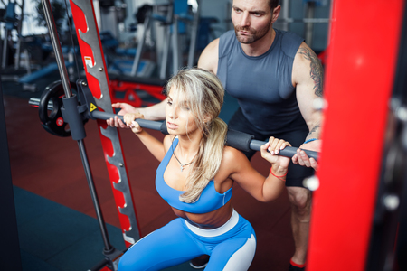 Sporty girl doing squat exercises with assistance of her personal trainer at public gym.