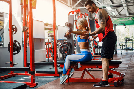 Sporty girl doing weight exercises with assistance of her personal trainer at public gym. Stock Photo