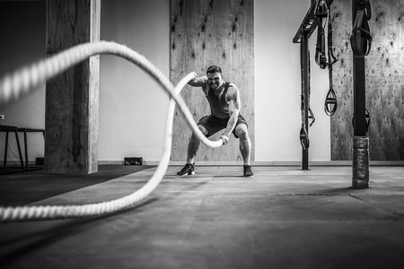 Men with rope in functional training fitness gym