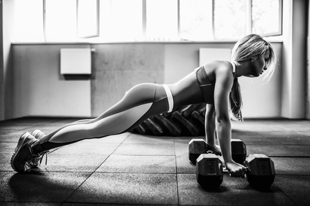laying abs exercise: Attractive young blonde girl doing dumbbells plank row exercise lifting dumbbell weights.