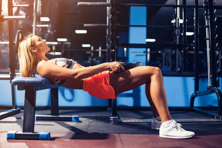 Sport girl doing exercise for abs with dumbbell in gym
