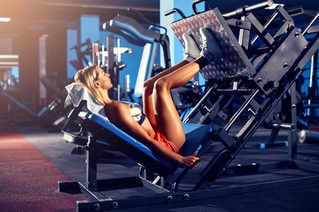 フィットネストレーニングを行っている女性は、ジムで重み付きの脚延長プッシュマシン