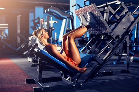 Woman doing fitness training on a leg extension push machine with weights in a gym Foto de archivo