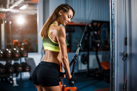 Fit well-trained blonde woman workout triceps lifting weights in gym
