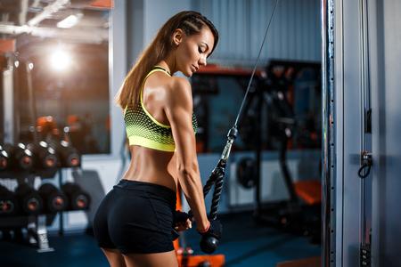 Fit goed opgeleide blonde vrouw training triceps tillen gewichten in de sportschool Stockfoto