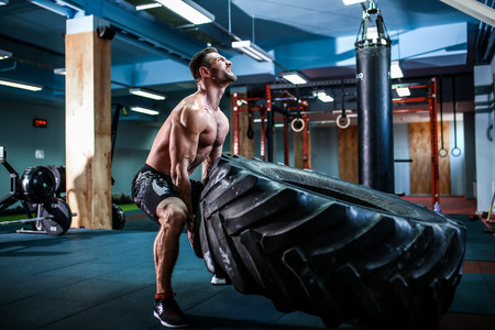 Shirtless man flipping heavy tire at crossfit gym Stock Photo