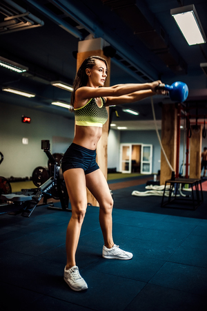Attractive female athlete performing a kettle-bell swing in crossfit gym.