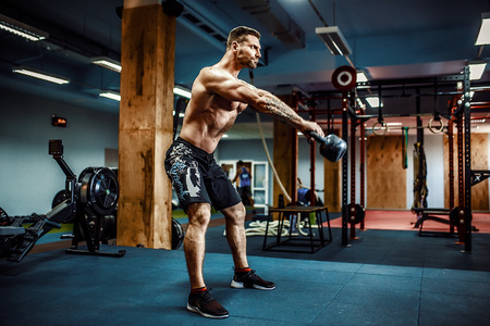 Fitness Kettlebells swing exercise bearded man workout at gym Stock Photo