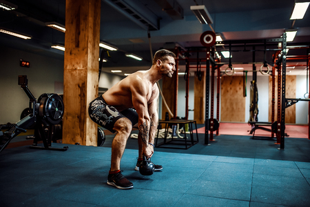 フィットネス ケトルベル スイング運動ひげを生やした男のジムでトレーニング
