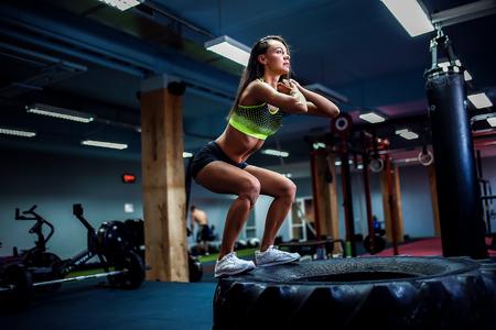 십자가 스타일 체육관에서 타이어에 점프 맞추기 젊은 여자. 여자 선수가 점프를하고있다.