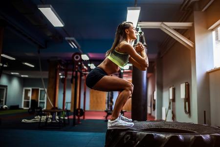 Geeignete junge Frau, die auf Reifen an einer crossfit Artgymnastik springt. Sportlerin führt Sprünge durch