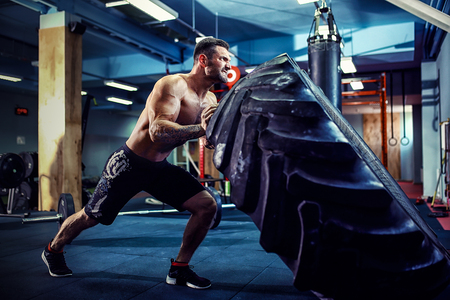 Shirtless man flipping heavy tire at crossfit gym Archivio Fotografico