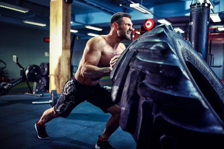 上半身裸の男が crossfit ジムで重いタイヤを反転 写真素材
