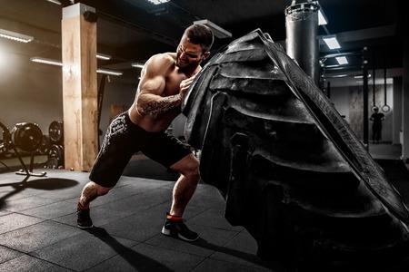 Hombre sin camisa voltear neumáticos pesado en el gimnasio de crossfit