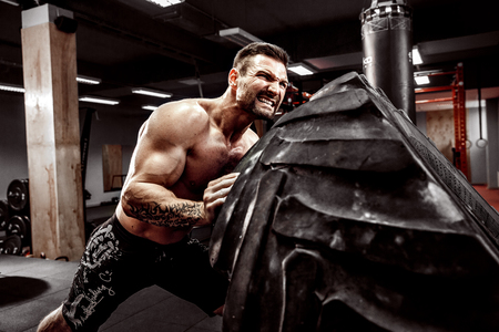crossfit 체육관에서 무거운 타이어를 뒤집은 Shirtless 남자 스톡 콘텐츠
