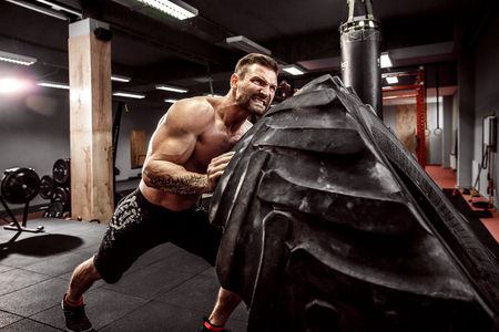 Shirtless man flipping heavy tire at crossfit gym Stockfoto