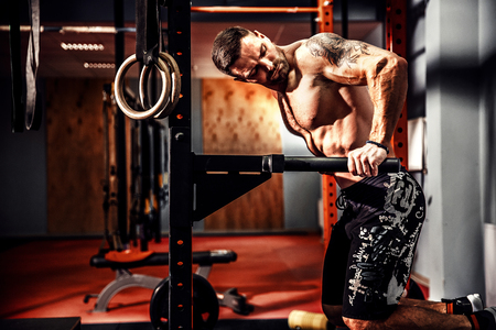 athletic wear: Strong muscular man doing push-ups on uneven bars in crossfit gym. Workout lifestyle concept. Stock Photo