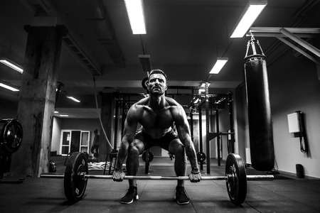 Strong muscular man at a crossfit gym lifting a barbell. Stock Photo