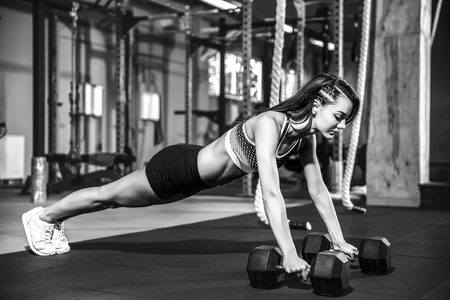 Attractive young girl doing dumbbells plank row exercise lifting dumbbell weights.