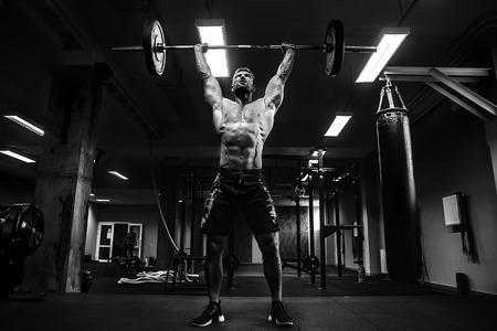 Hombre muscular fuerte en un gimnasio crossfit levantando una barra.