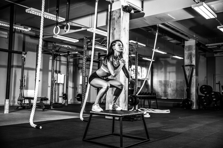 Fit young woman box jumping at a crossfit style. Female athlete is performing jumps at gym Stock Photo