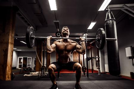 현대 피트니스 센터에서 그의 머리 위로 역기를 역임하는 근육 피트니스 남자. 기능 훈련. 스 내치 운동