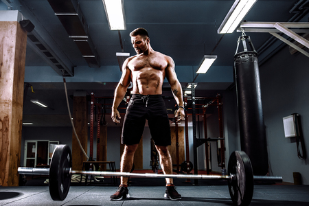 Muscular fitness man threw the bar on the floor after deadlift of a barbell in modern fitness center. Functional training. Snatch exercise